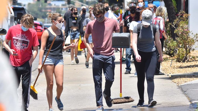 A group of people brought brooms and dust pans to downtown La Mesa to clean and repair damage to businesses damaged by protesters.