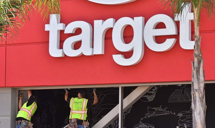Workers prepare to climb broken windows during looting in La Mesa. Target shops are temporarily closed throughout the country.