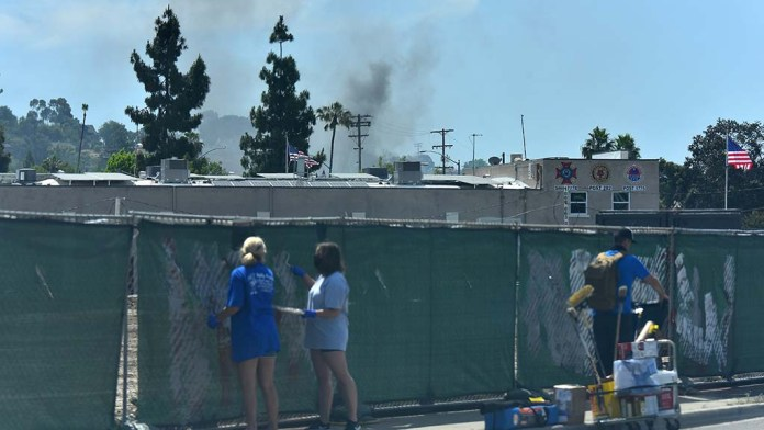 Volunteers paint over graffiti as a blazing building in downtown La Mesa on Sunday morning.