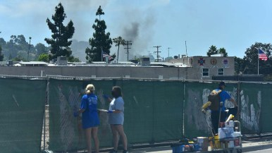 Volunteers paint over graffiti as a building smolders in downtown La Mesa Sunday morning.