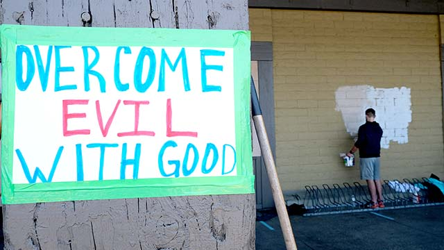 A volunteer paints over protester tagging at La Mesa Springs Shopping Center, where looting and vandalism occurred Saturday night.