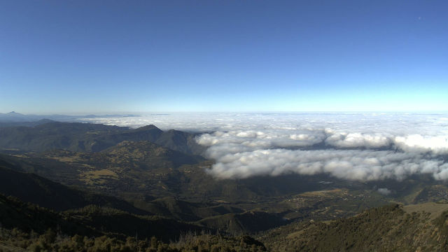 Palomar Mountain in the sun while clouds cover the valley