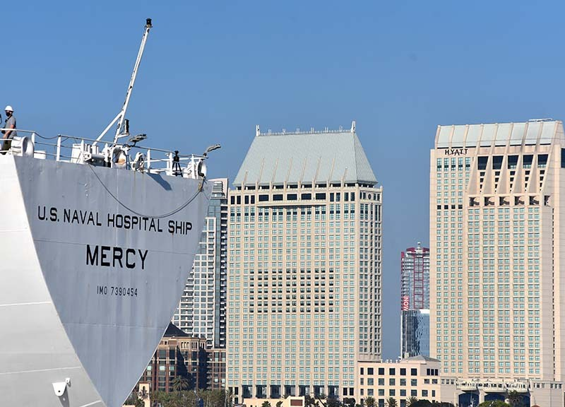 USNS Mercy backed into port as it passed downtown hotels.