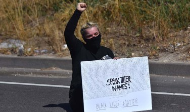 """A woman sits on Interstate 8 freeway onramp with sign saying """"Speak their names."""""""