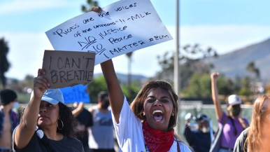 """A woman yells while holding a sign quoting Martin Luther King Jr.: """"Riots are the voices of the unheard."""""""