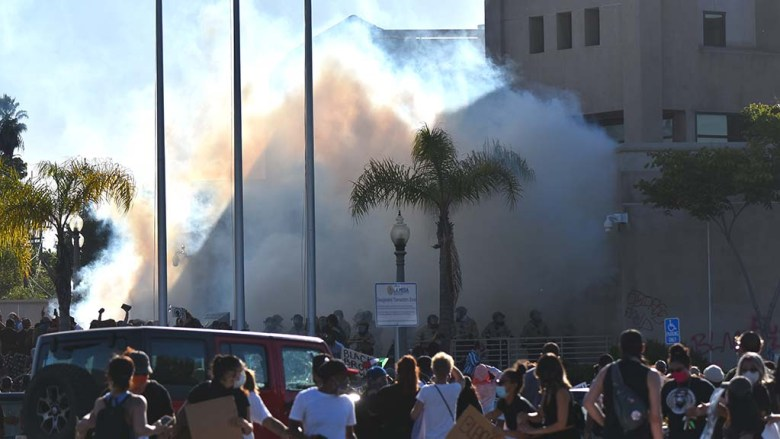 Protesters watch tear gas shot outside the entrance to the La Mesa police station. Photo by Chris Stone