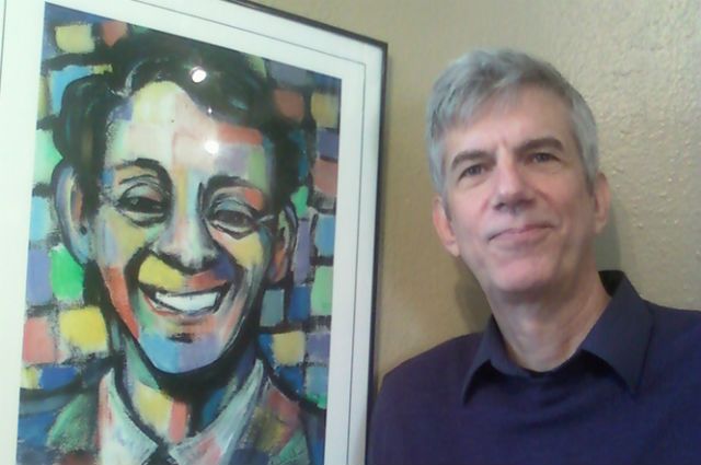 """Dan Kirsch with a poster from a """"Dear Harvey"""" production"""