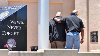 A man leads La Mesa Mayor Mark Arapostathis (left) into the police department building shortly before the protest begins.