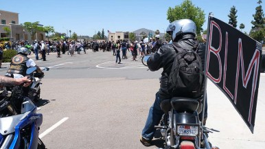 A BLM-sign carrying biker arrived separately from the Unity Ride caravan at the La Mesa Police Department parking lot.