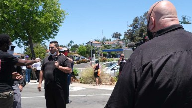 Tareq Asfour (center) argues with a protester after a loud outburst criticizing La Mesa Mayor Mark Arapostathis (right).
