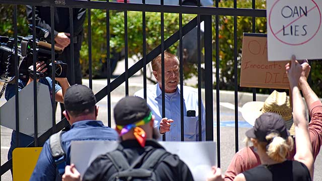 Robert Herring Sr., CEO and founder of OANN, speaks to protesters through locked gate. Photo via Eddie McCoven.