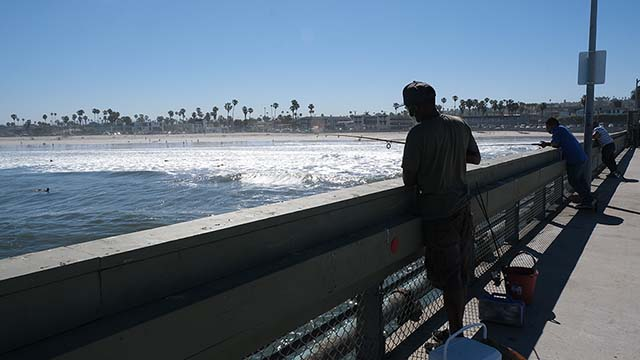 Fisherman stood along the railings early in the morning at Ocean Beach Pier on the opening day of city piers being accessible after months of closure.