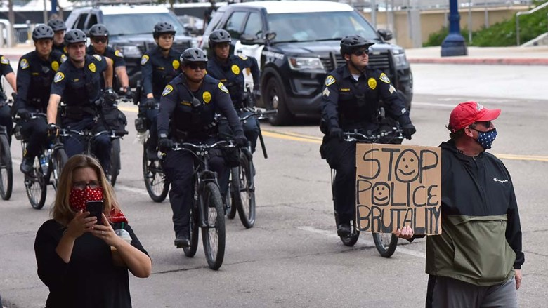 The last protester holds up a sign as San Diego police follow the march on their bikes.