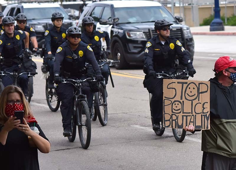 The last protestor holds up a sign as San Diego police officers follow the march on bike.
