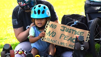 A woman with her daughter prepare to participate in a Black Lives Matter event in San Diego Mission Bay Park.