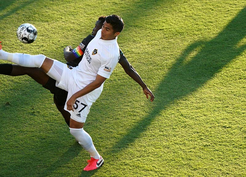 LA Galaxy's Omar Ontiveros (front) and Loyal's Tumi Moshobani reach for the ball in unison