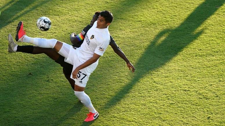 LA Galaxy's Omar Ontiveros (front) and Loyal's Tumi Moshobani reach for the ball in unison