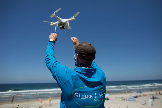 A researcher retrieves an incoming drone
