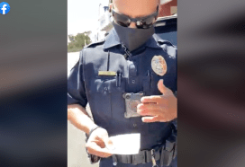 San Diego police officer examines what Amber Lynn Gilles calls her medical exemption from having to wear a face mask.
