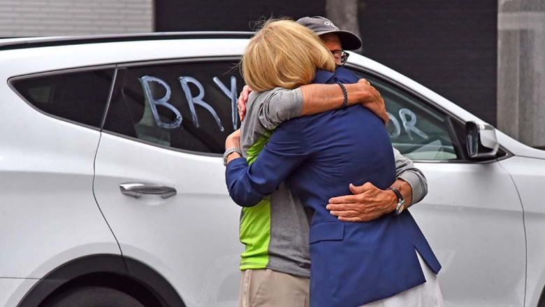 Mayoral candidate Barbara Bry is hugged by her husband at a downtown rally before a caravan in the Balboa Park area.