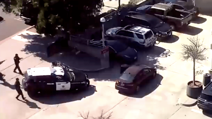 San Diego police officers approach Kia with armed woman in downtown station parking lot.