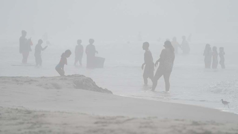 Beachgoers were enveloped by fog during competition at the Nissan Super Girl Surf Pro in Oceanside.