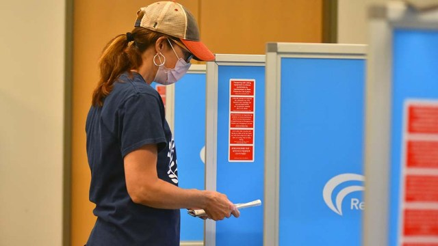 A woman checks her voter guide while voting at the San Diego Registrar of Voters office in Kearny Mesa.