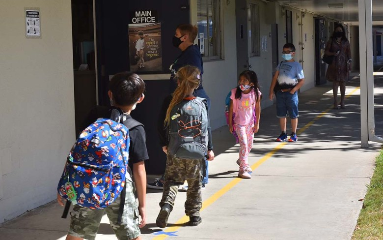 Children line up in a Lafayette Elementary School walkway outside the school office on the first day back to school since March.
