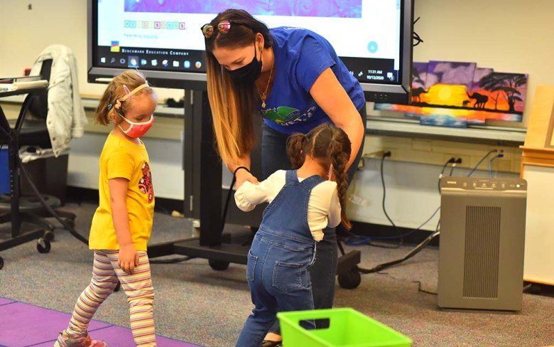 A teacher moves students to help them observe social distancing at Lafayette Elementary School on the first day of class.