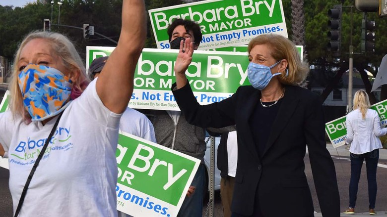 Mayoral candidate Barbara Bry waves to passersby on Torrey Pine Road in La Jolla on Election Day.