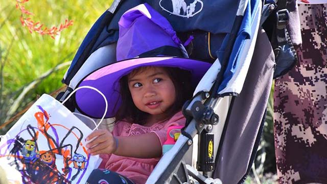 """A young """"witch"""" has her bag open for treats at the Ocean Beach Recreation Center on Halloween."""