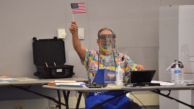 A poll worker in Santee signals to a voter that he can check in.