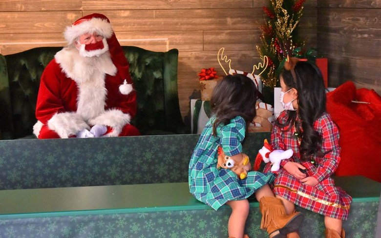 Sisters look to Santa at Mission Valley Mall the day after Thanksgiving.