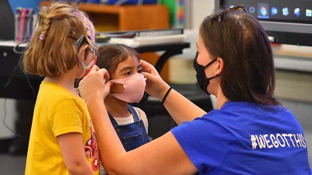 A teacher adjusts a mask on one of her students at Lafayette Elementary School in Clairemont on the first day back to school.