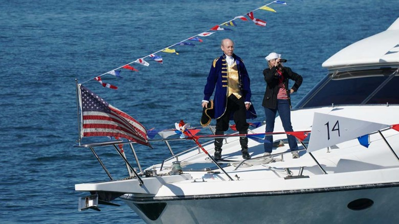 Boaters in costumes in a Veterans Day boat parade glide by spectators near the USS Midway.