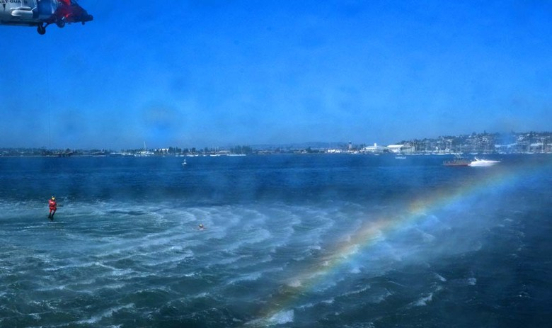 A U.S. Coast Guard helicopter puts on a rescue demonstration and creates a rainbow above the water.