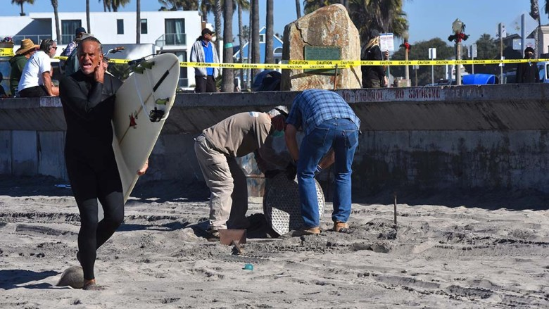 A manhole style cover is removed above the hole that the Ocean Beach Christmas tree will be placed in.