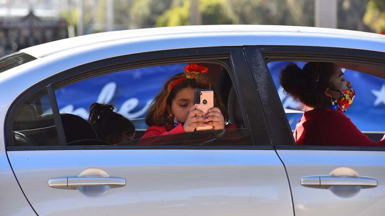 A girl dressed for the season takes photos with a cellphone as she passes food booths at Taste of December Nights.