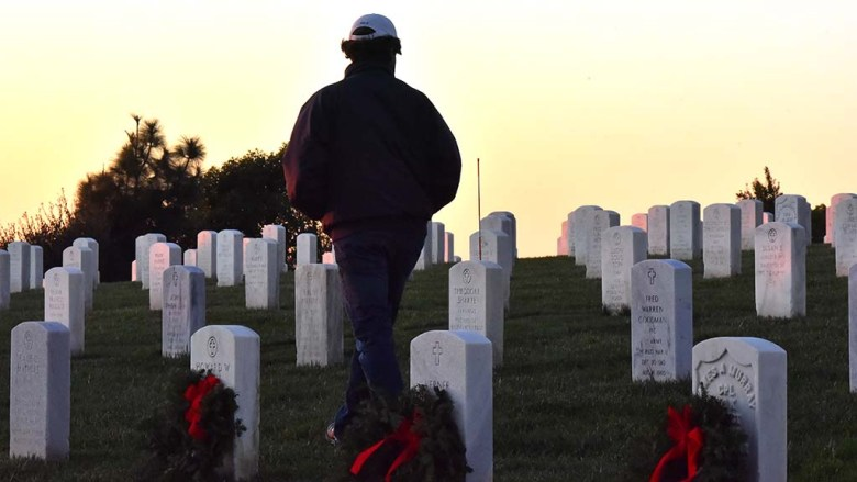 A visitor to Fort Rosecrans National Cemetery walks among the grave sites, some decorated with holiday wreaths.