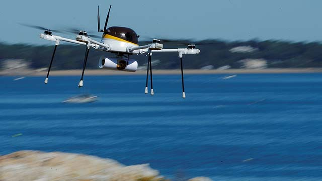A CyPhy Works drone carries package off coast of Beverly, Massachusetts, in 2016, during UPS demonstration of a drone making a commercial delivery.