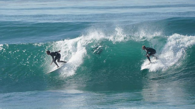 Surfing in tandem is seen just north of Windansea where surfers flocked to same good waves.