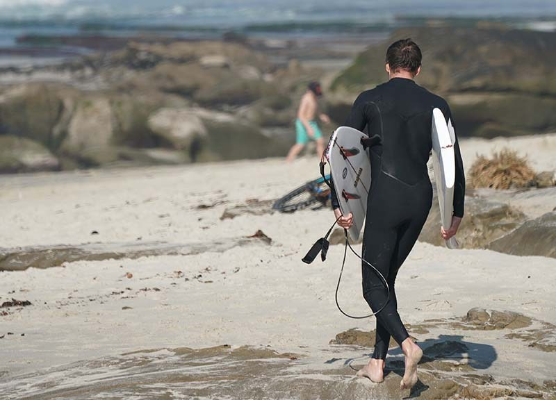 A surfer leaves the strong waves with his surfboard broken in half.