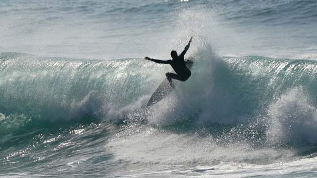 Roll out the barrel as a surfer glides over the top of a tight wave.