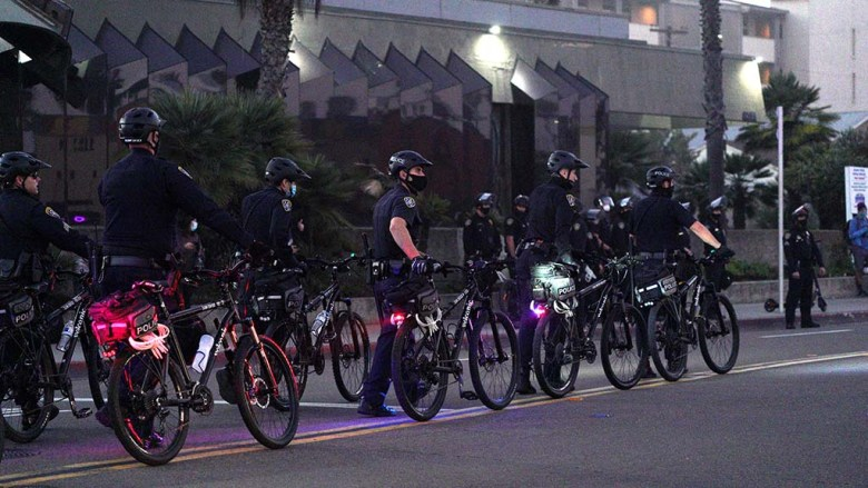 San Diego Police Officers on bicycles move on Mission Boulevard in front of a gathering of Trump supporters.