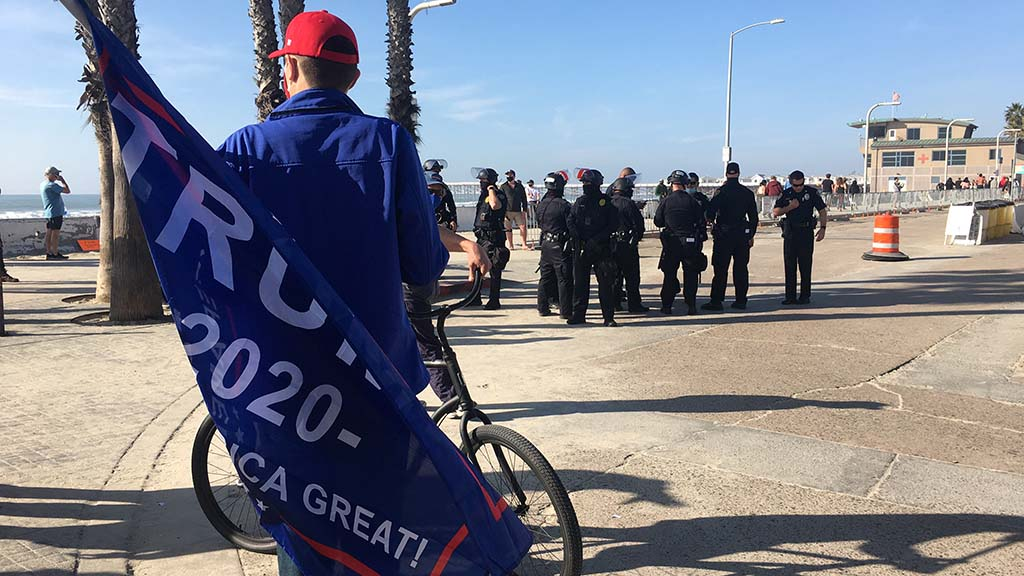 A supporter of Donald Trump stands where San Diego police gather at Thomas Avenue and Ocean Boulevard.