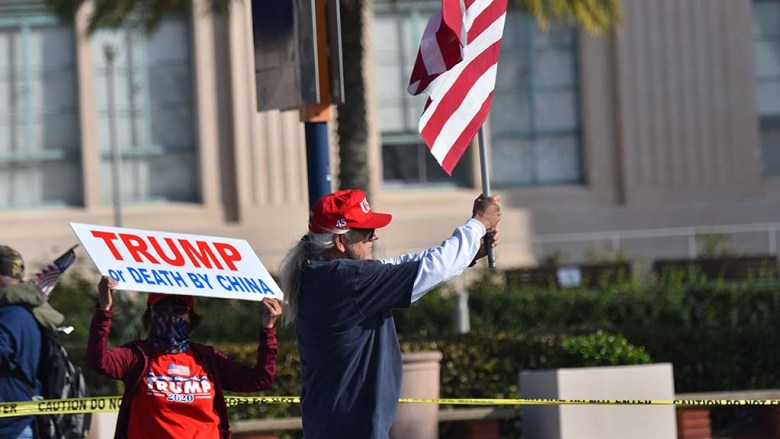 Supporters of Donald Trumps efforts to retain the presidency greet drivers on Harbor Drive in front of the San Diego County Administration Building.