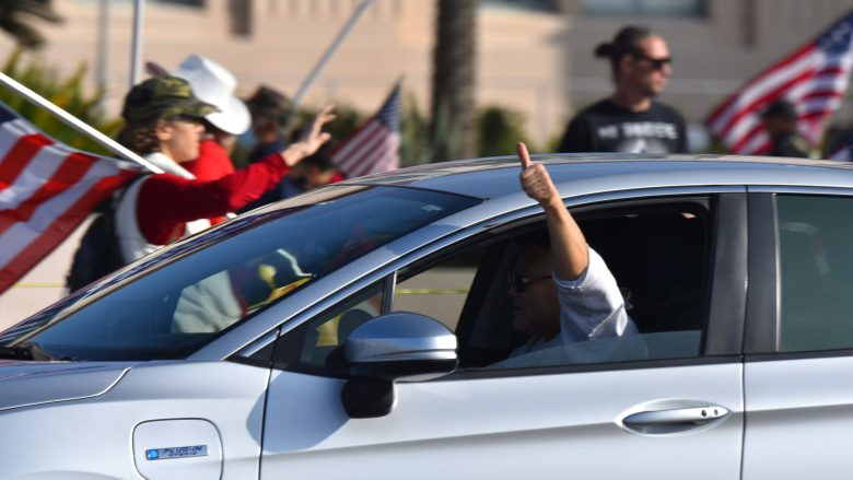 A driver gives a thumbs up to Trump supporters demonstrating in front of the San Diego County Administration Building on Jan. 6.