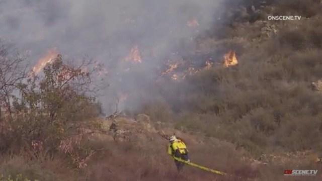 Firefighter climbs hillside toward Chula Vista blaze.