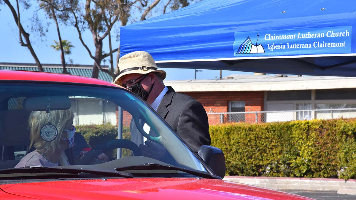 """Senior Pastor, Rev. Dr. Jonathan Doolittle at Clairemont Lutheran Church prays for a woman who received ash at the Ash Wednesday drive-in """"Ashes to Go."""""""