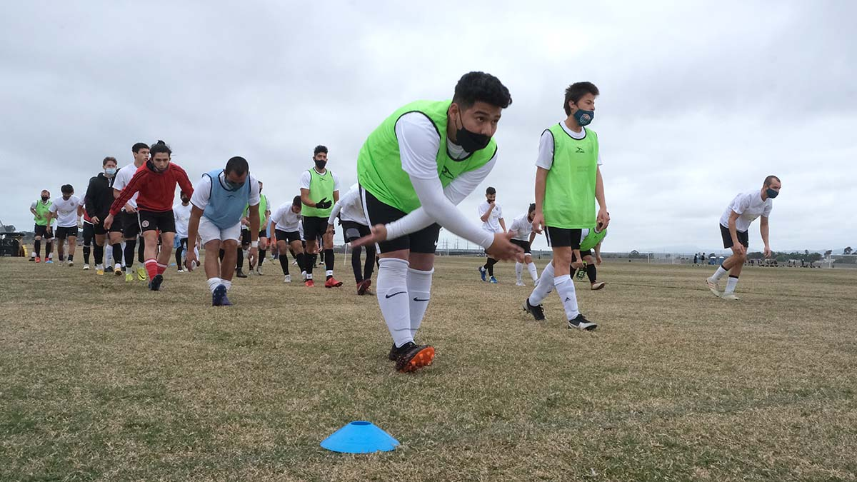 A group of young men warm up on a field in Oceanside for their chance to tryout for the San Diego Loyal Soccer Club.